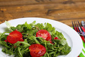 Green salad made with  arugula, tomatoes and sesame  on plate, on wooden background — 图库照片