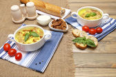 Tasty soup in saucepans on wooden table, close up — 图库照片