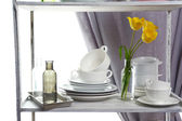 Different tableware on shelf in the interior — Stock Photo