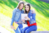 счастливые студенты, сидит в парке — Стоковое фото