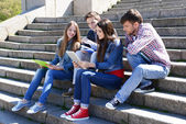 Happy students sitting on stairs in park — Stockfoto
