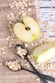 Apple with oatmeal and vintage spoons on sackcloth, on color wooden background — 图库照片