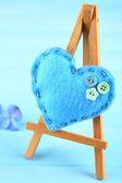 Cavalete decorativo pequeno de coração lindo sobre fundo azul — Fotografia Stock