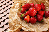 Red ripe strawberries with chocolate on brown paper — 图库照片
