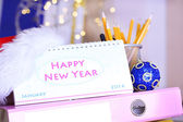 Table with office supplies, calendar and Christmas tinsel close-up — Zdjęcie stockowe