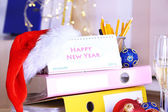 Table with office supplies, calendar and Christmas tinsel close-up — Stockfoto