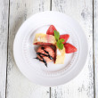 Tasty homemade strudel with ice-cream, fresh strawberry and mint leaves on plate, on wooden background — Stock Photo