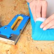 Fastening fabric and board using construction stapler — Stock Photo #48323029