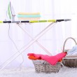 Baskets with laundry and ironing board on light home interior background — Stock Photo