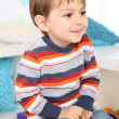 Cute little boy sitting on small chair in room — Stock Photo