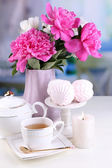 Peonies in vase, tea in cup and marshmallow — Stock Photo