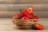 Red ripe strawberries in wicker basket on wooden background — Stock Photo