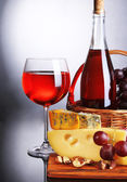 Pink wine, grapes and cheese on grey background — Stock Photo