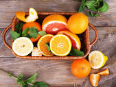 Fresh citrus fruits with green leaves in wicker basket on wooden table background — Stock Photo