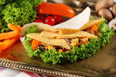 Veggie wrap filled with chicken and fresh vegetables on tray, close up — Stock Photo