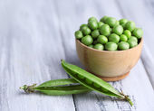 Green peas in wooden bowl on wooden background — Stock Photo