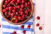 Ripe sweet cherries in bowl on wooden table — Stock Photo