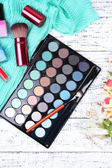 Eyeshadow, brush, lipstick and flowers on color wooden background — Stock Photo