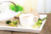 Tasty herbal tea with linden flowers on wooden table — Stock Photo