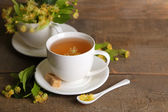 Tasty herbal tea with linden flowers on wooden table — Стоковое фото