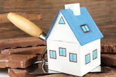 Wooden toy house on trowel and tiles on wooden background, close up  — Stock Photo