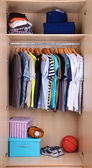 Colorful clothes hanging in wardrobe — Photo