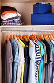 Colorful clothes hanging in wardrobe — Stock Photo