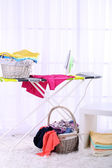 Baskets with laundry and ironing board on light home interior background — Foto de Stock