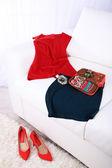 Kosmetyczka, moda ubrania, butelki perfum na kanapie na jasnym tle — Zdjęcie stockowe