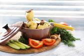 Jonge gekookte aardappelen in de pan met de groenten op houten tafel, close-up — Stockfoto