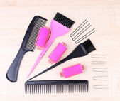 Professional hairdresser tools - comb, scissors, pins and curlers on light wooden background — Stock Photo