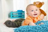 Cute baby boy lying on floor in room — Stock Photo