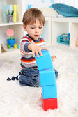 Cute little boy playing in room — Stockfoto