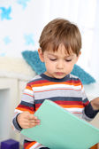 Cute little boy reading book in room — Stock Photo