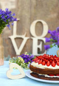 Strawberry cake with wildflowers and decorative letters on table  — Stock Photo