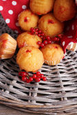 Tasty muffins with red currant on wicker mat background — Stock Photo