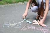 Cute girl drawing with chalk on asphalt — Stock Photo