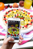 Hand making photo of fruit pizza on mobile phone for social network — Stock Photo