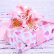 Pink gift with bow and flower on wooden table close-up — Stock Photo #48368269