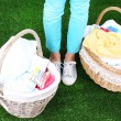 Woman holding laundry baskets with clean clothes, towels and pins, on green grass background — Stock Photo #48369715