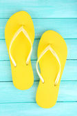 Bright flip-flops on color wooden background — Stock Photo