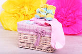 Baby clothes in basket on floor in room — Stock Photo