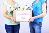 Volunteers with donation box with foodstuffs — Stock Photo
