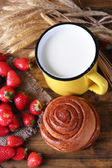 Ripe sweet strawberries, fresh bun and mug with milk on color wooden background — Stock Photo