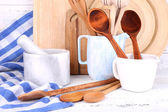 Composition of wooden cutlery, mortar, bowl and cutting board on wooden background — Stock Photo