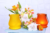 Bright icon-lamps with flowers on wooden stand on light background — Stock Photo