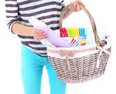 Woman holding laundry basket with clean clothes, towels and pins, isolated on white — ストック写真