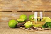 Свежий летний напиток с лаймом и гвоздику в стекло, на цвет фона и деревянные — Стоковое фото