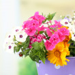 Bouquet of colorful flowers in decorative vase, on table, on bright background — Stock Photo