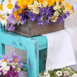 Beautiful flowers in crates on small chair on light background — Stock Photo #48370873